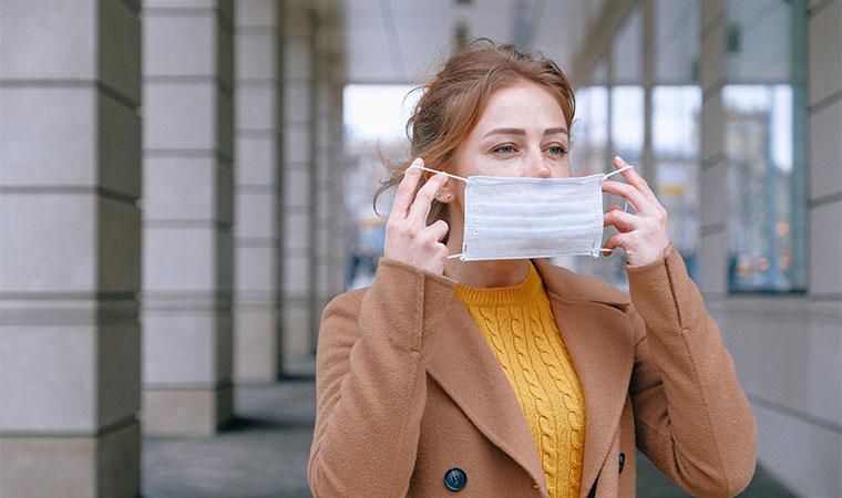 マスクをつけようとする女性